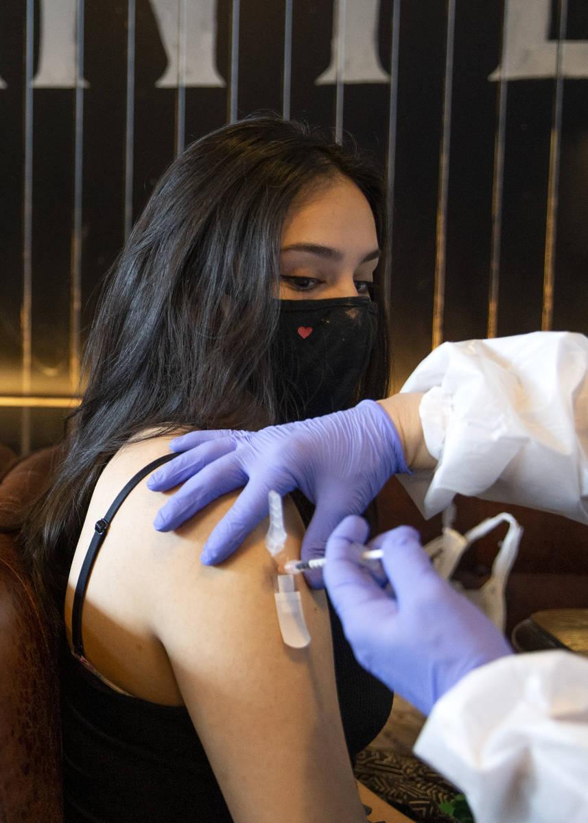 Audrey Vallapudua, of Las Vegas, receives the Pfizer COVID-19 vaccine during a pop-up vaccinati ...