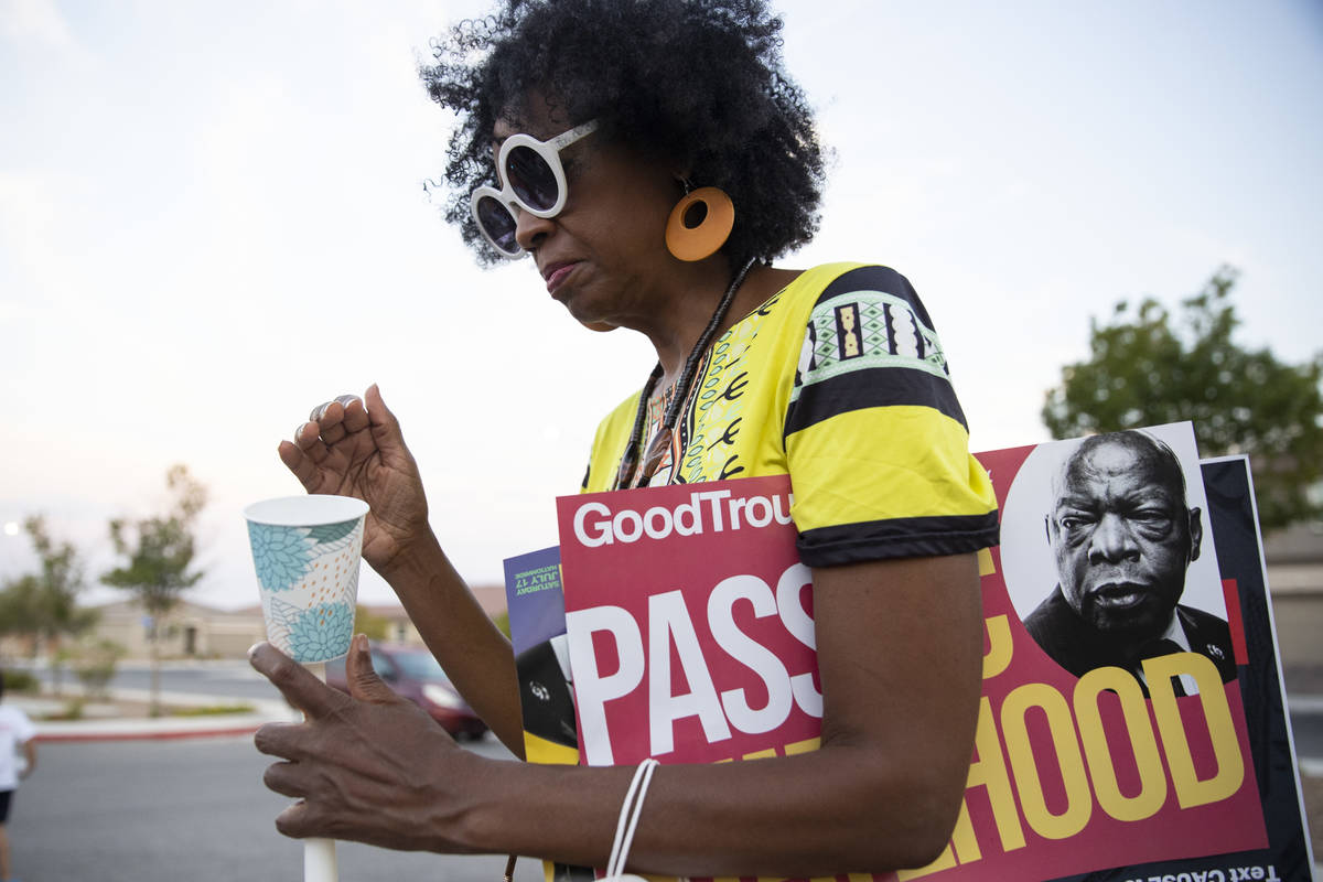 Karmen Smith of Henderson participates during a Good Trouble candlelight vigil on the anniversa ...