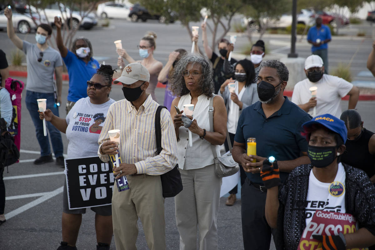 People attend a Good Trouble candlelight vigil on the anniversary of the death of civil rights ...