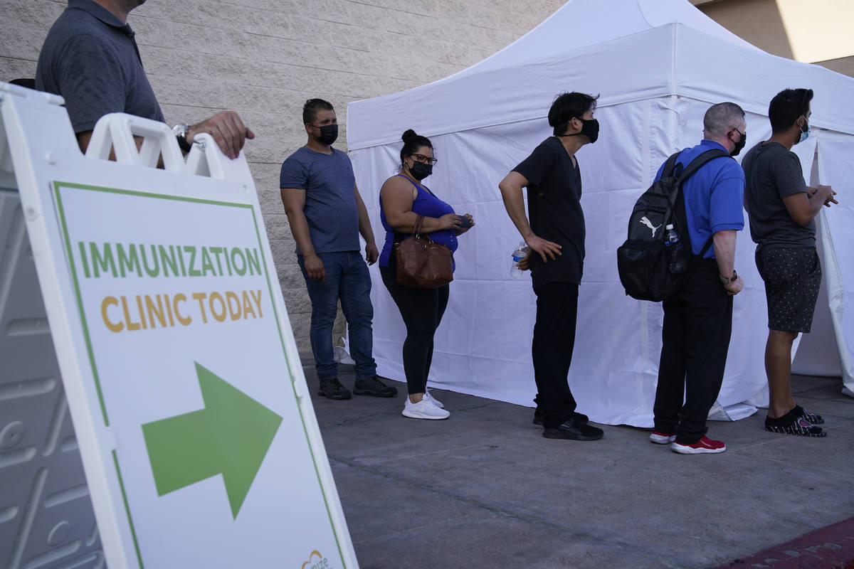 FILE- In this Wednesday, July 7, 2021, file photo, people wait in line for COVID-19 vaccination ...