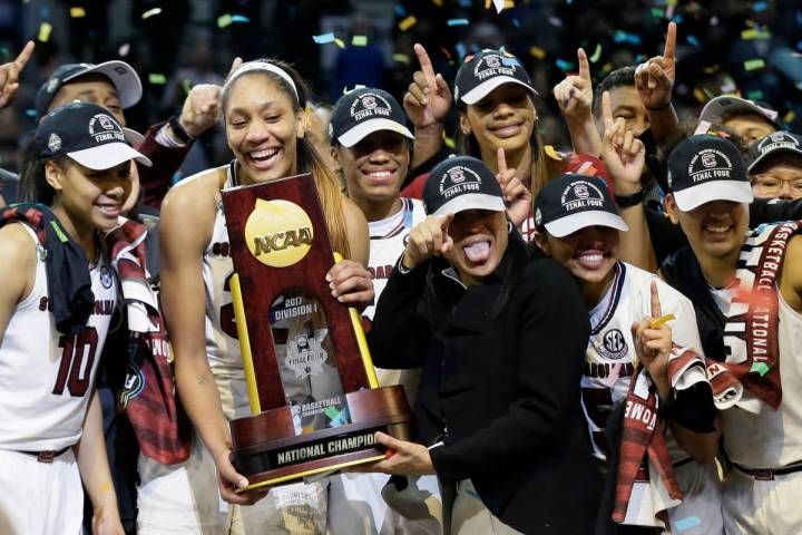 South Carolina forward A'ja Wilson holds the trophy and coach Dawn Staley points as the team ce ...