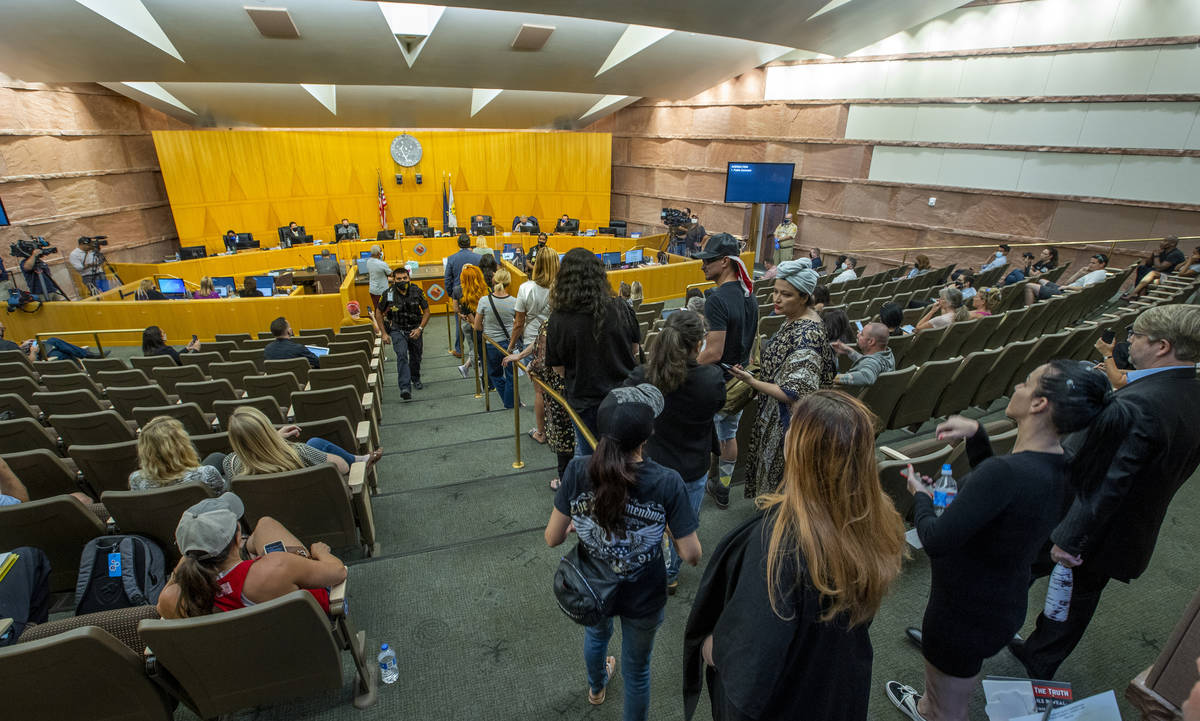 People line up to speak during the public comment portion of a meeting to discuss the increasin ...