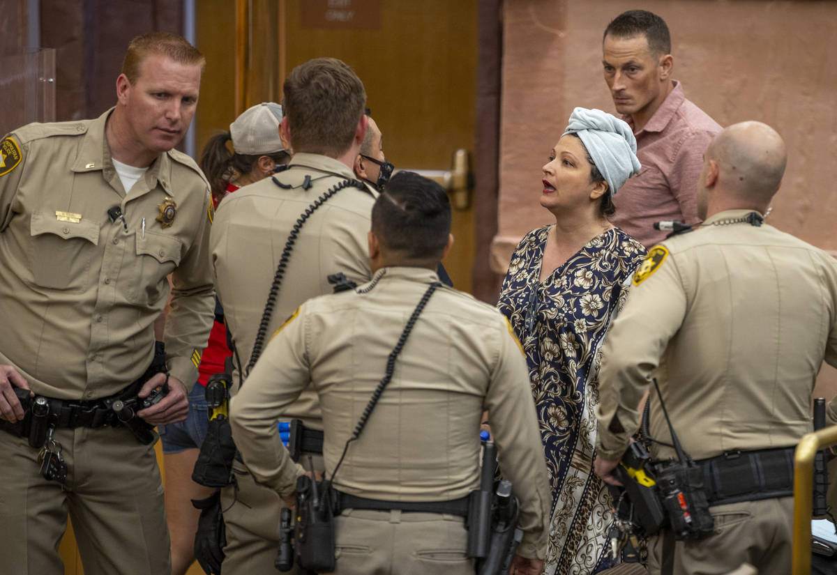 Officers speak with Katrin Ivanoff during the Clark County Commission meeting for public outbur ...