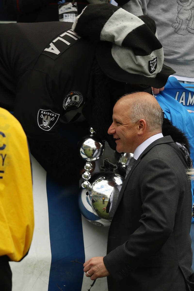 Raiders president Marc Badain shakes hand with Gorilla Rilla before an NFL game against the Los ...