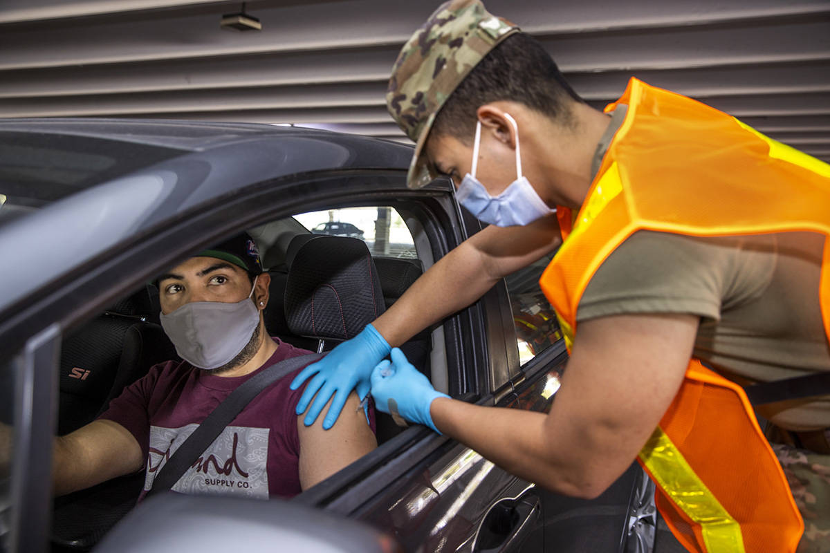 Andy Ruiz, left, looks on as Nevada National Guard SRA Dooley Gegen gives him a shot during a p ...
