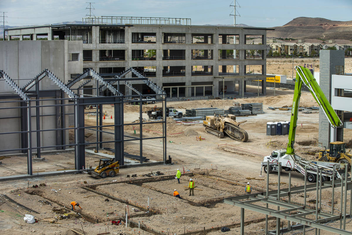 Office Building #2, center, with the Market Hall, left, and a garage continue being constructed ...