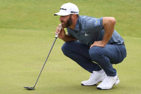 United States' Dustin Johnson looks along the line of his putt on the 6th green during the firs ...