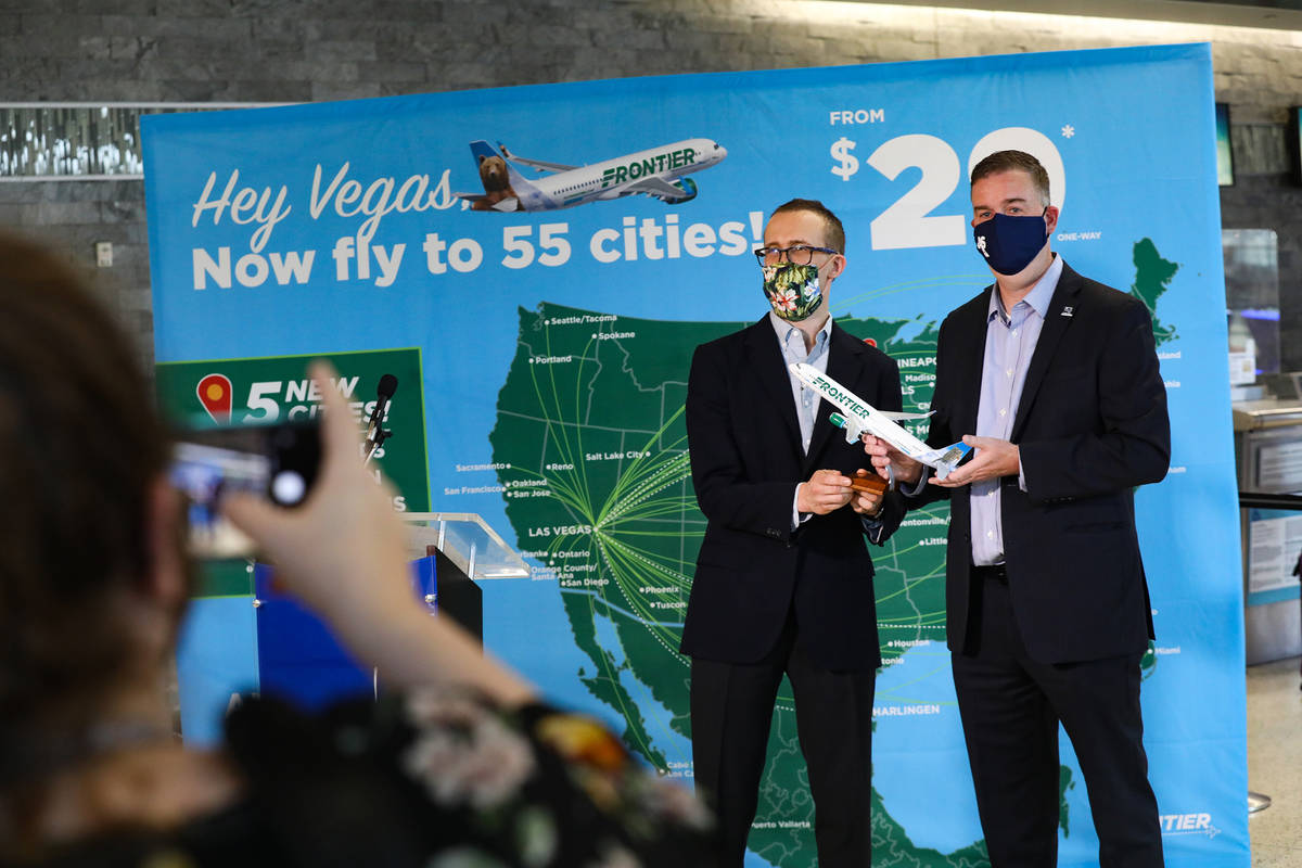 Daniel Shurz, senior vice president of commercial Frontier Airlines, left, takes a photo with C ...
