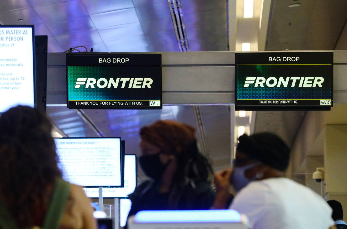 Guests check in at the Frontier counter in terminal three of McCarran International Airport in ...