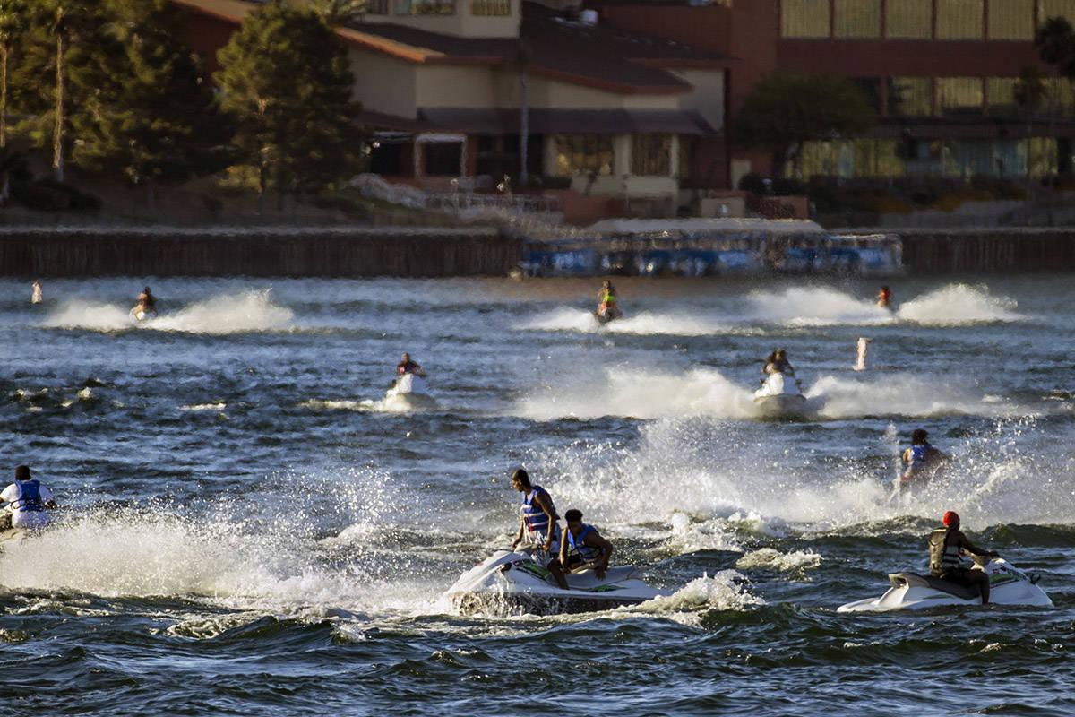 Jetskiers cruise across along the Colorado River near the Bullhead City Community Park on Tuesd ...