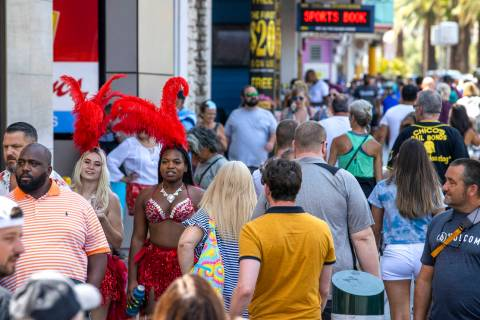 People walk along the Strip near The Venetian, most not wearing mask, on Friday, July 16, 2021, ...