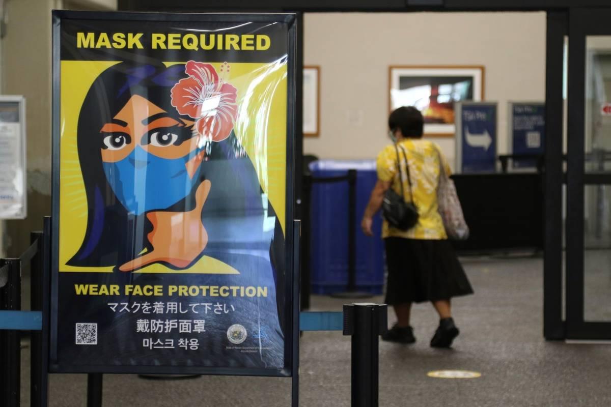 A woman walks into the international airport in Honolulu in October 2020. (AP Photo/Caleb Jones)