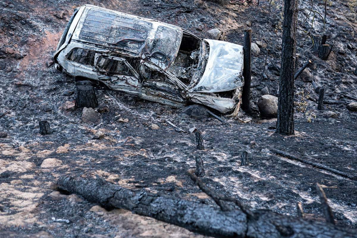 A burned car damaged by the Bootleg Fire is seen here along a mountain road on Wednesday, July ...