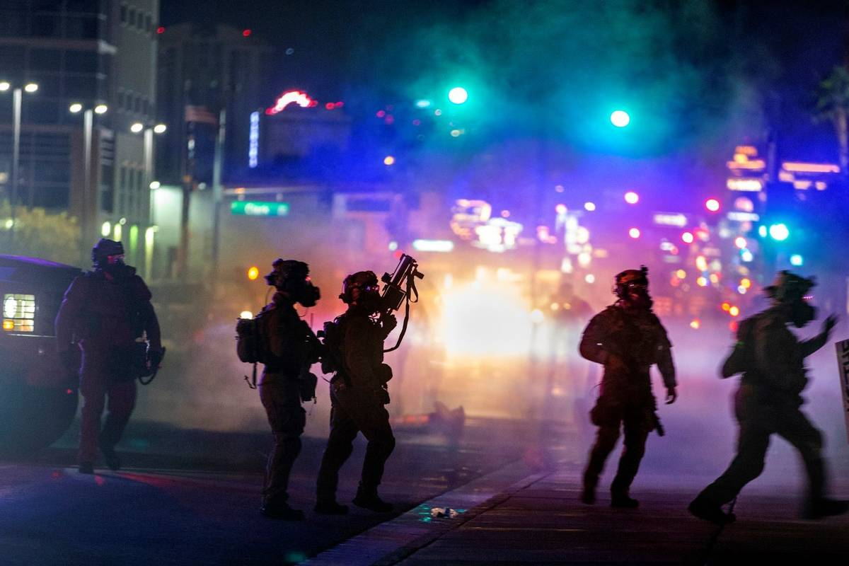 Las Vegas police are engulfed in tear gas during a protest along Las Vegas Blvd. on Saturday, M ...