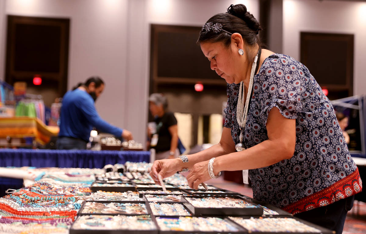 Karen Sanchez of Albuquerque, N.M. sets up Navajo jewelry and crafts in her booth during the In ...