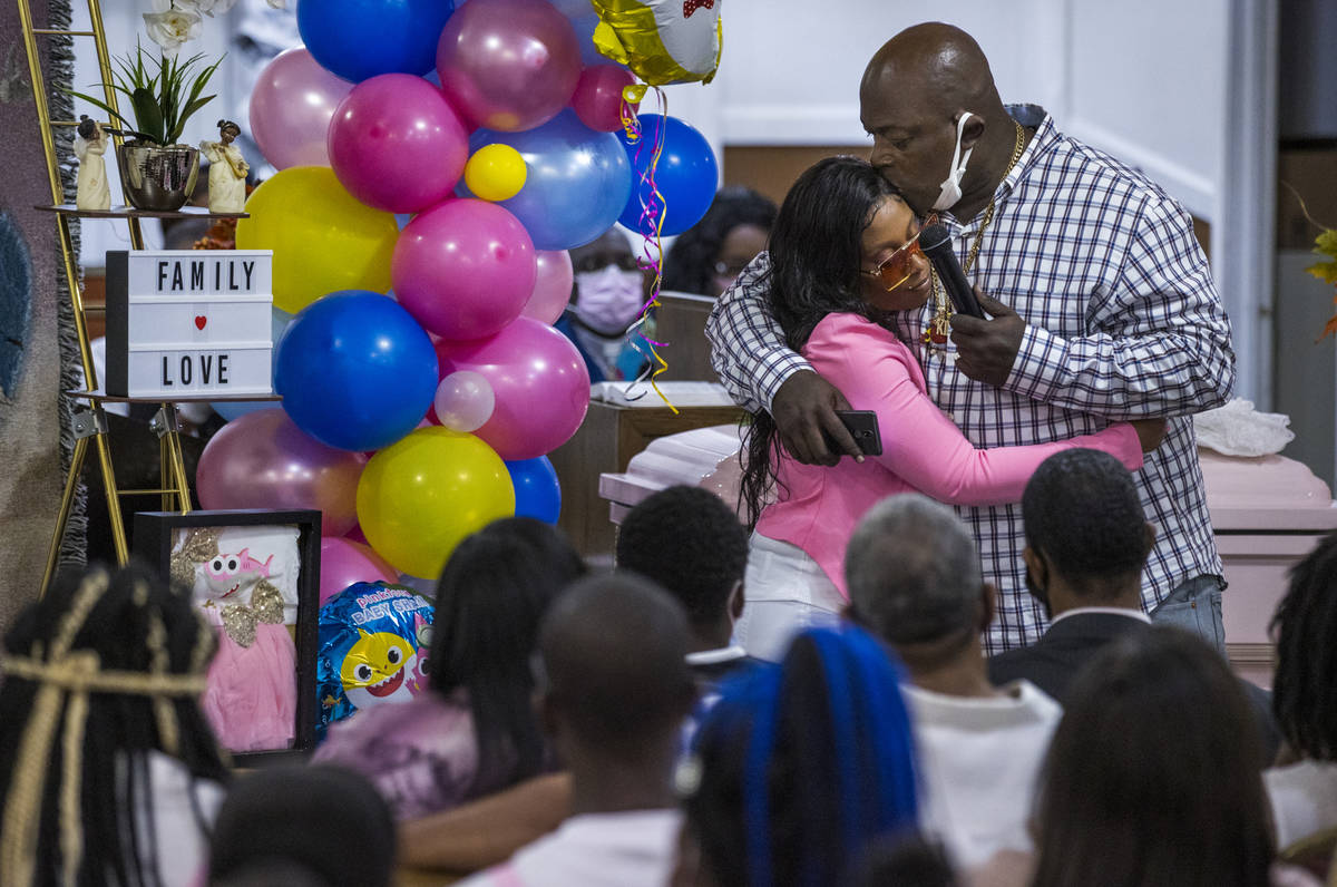 Mario Hunt, right, hugs Mariah Coleman after he recited a poem he wrote for her daughter Sayah ...