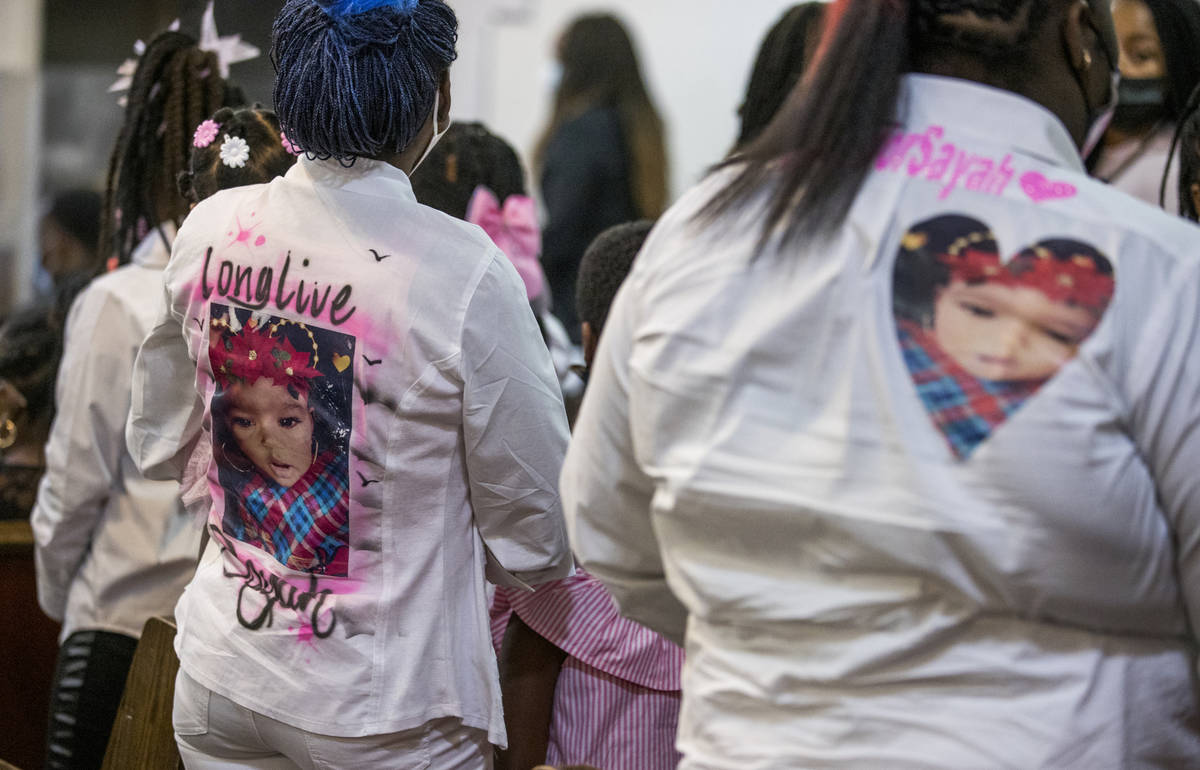 Mourners display caring messages on their clothing during the funeral service for Sayah Deal at ...