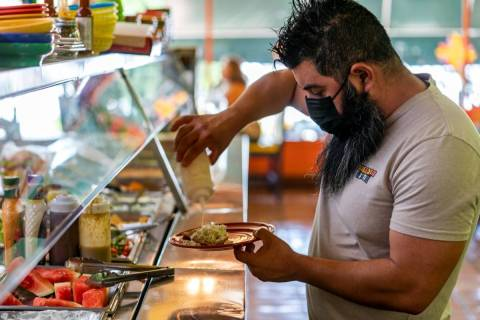 Gustavo Arellano, 36, who is vaccinated, wears a face mask as he fixes himself a plate at Taque ...