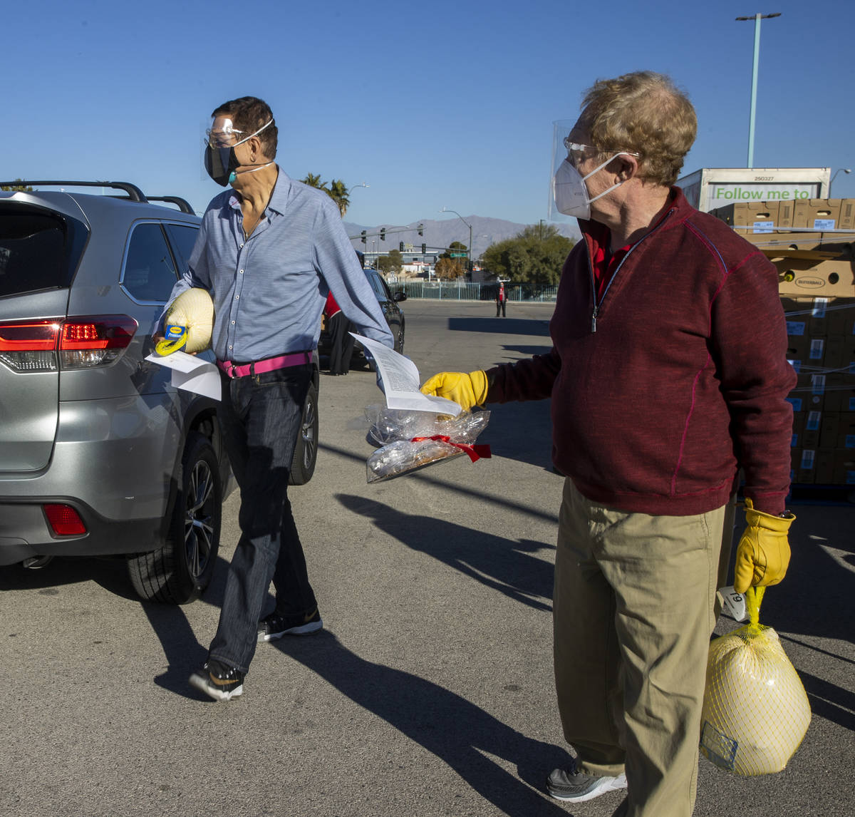 Penn & Teller carry over turkeys and cookies to awaiting vehicles during the re-opening of the ...