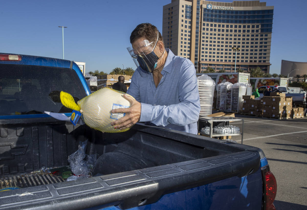 Penn Jillette delivers a turkey and cookies to an awaiting vehicle during the re-opening of the ...