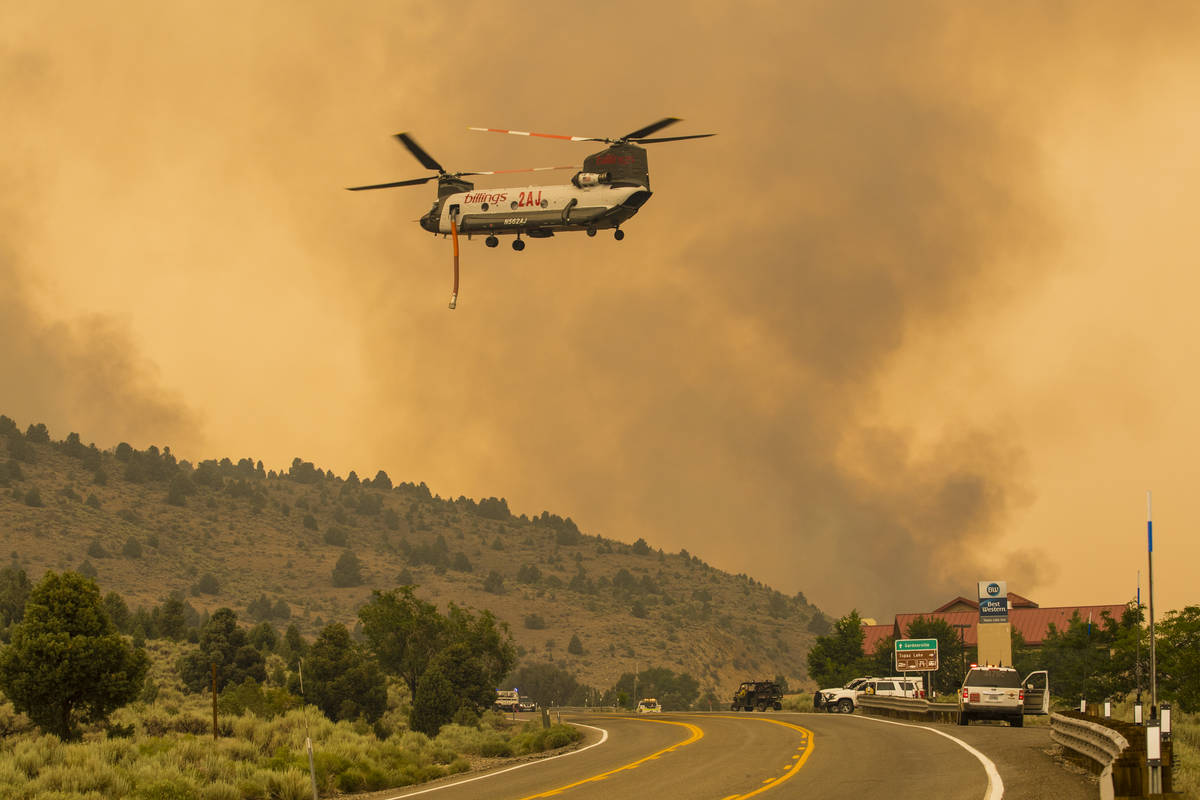 A firefighting chopper  flies arsenic  the Tamarack Fire burns astir   Topaz Lake, Nev., Friday, Jul ...