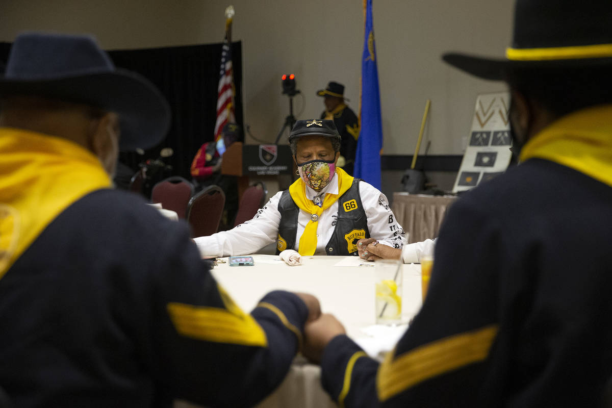 Dora Macklin, center, a member of the Buffalo Soldiers, bows her head in prayer during an event ...