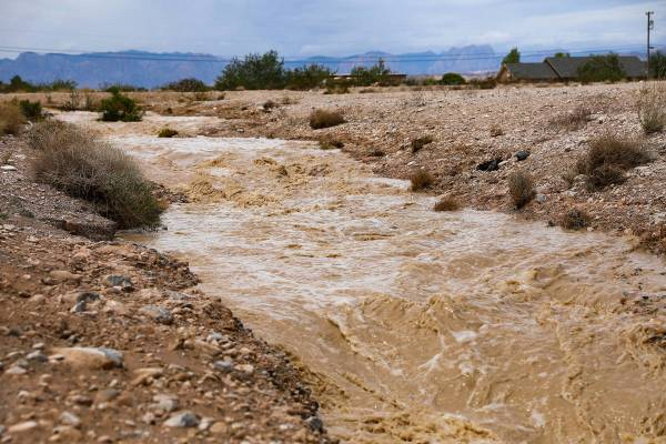 Water overflows into a nearby drain by Rainbow Boulevard and Blue Diamond Road in Las Vegas, Mo ...