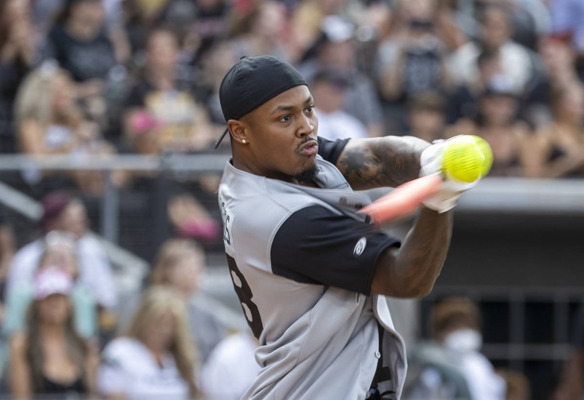 Las Vegas Raiders Josh Jacobs (28) connects on a hit during a charity softball game versus the ...