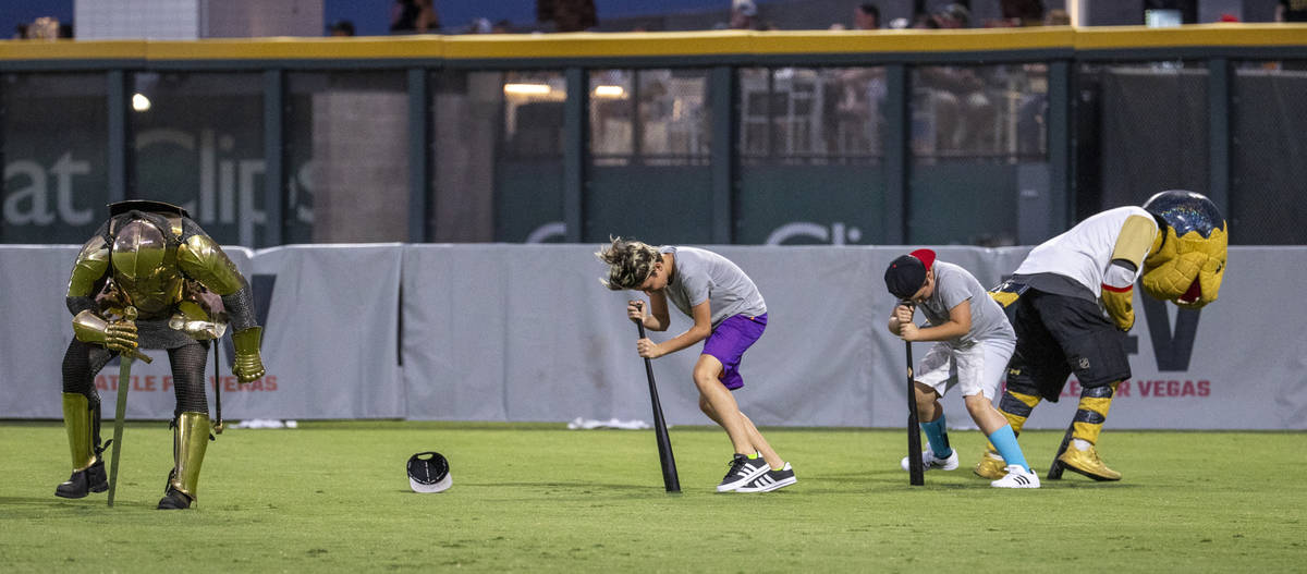 The Golden Knight and Chance the Gila Monster join in the ÒDizzy Bat RaceÓ during a c ...