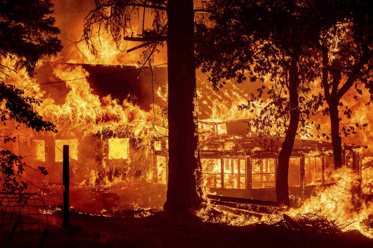Flames from the Dixie Fire consume a home in the Indian Falls community of Plumas County, Calif ...