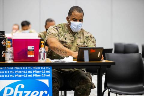 Nevada National Guard Spc. Demetrie Barnett works at his station at the vaccination clinic at t ...