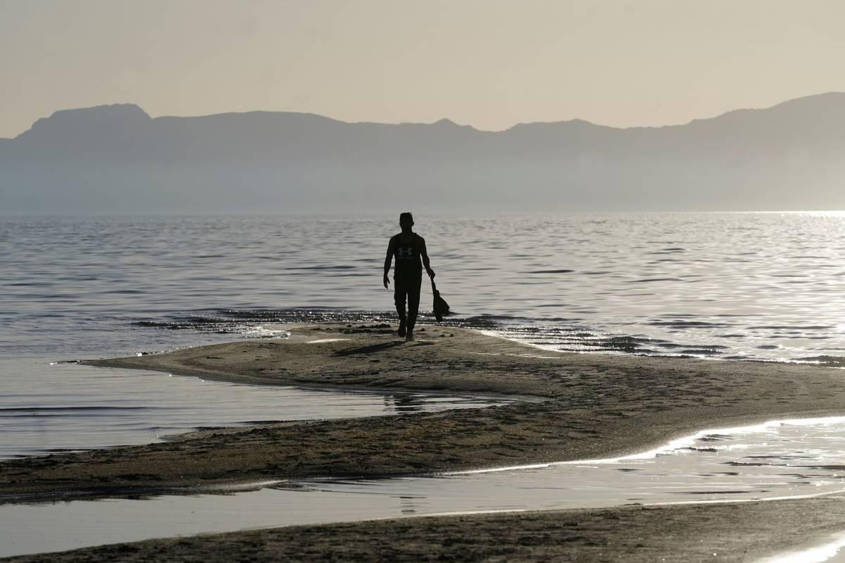 A man walks along a sand bar at the receding edge of the Great Salt Lake on June 13, 2021, near ...
