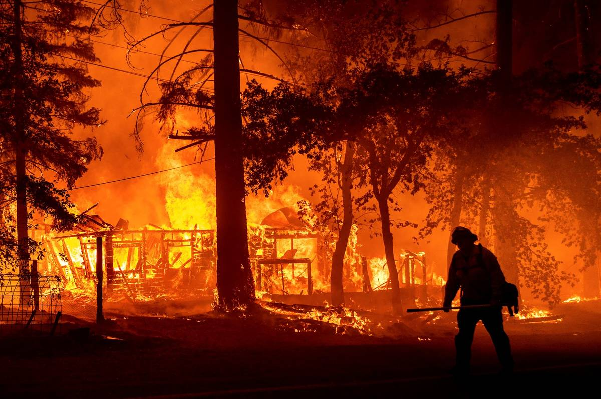A firefighter passes a burning home as the Dixie Fire flares in Plumas County, Calif., on Satu ...