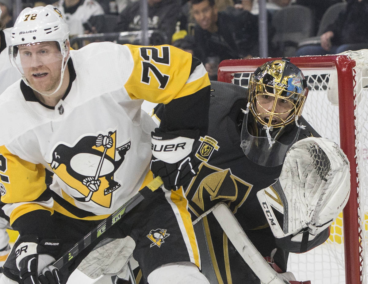 Golden Knights goaltender Marc-Andre Fleury (29) fights for position with Penguins right wing P ...