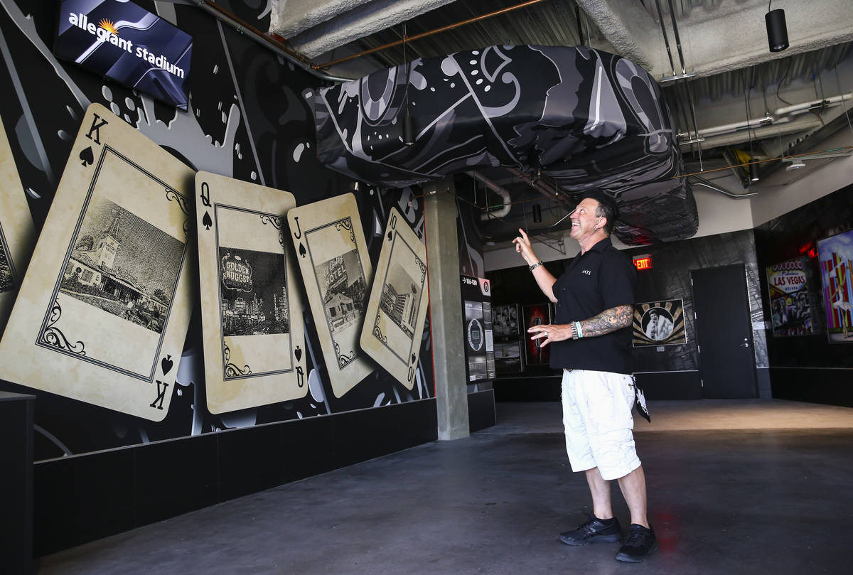 Artist Michael Godard, who curated the Allegiant Stadium art collection, shows off one of the a ...