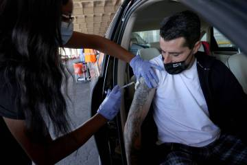 David Lotta of Las Vegas gets his shot from Destanee Sanders during a drive-thru COVID-19 vacci ...