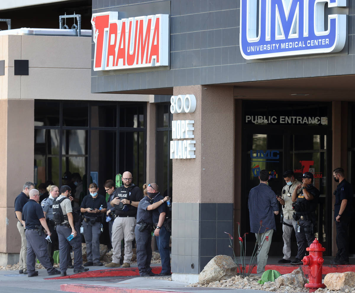 Police officers from multiple Las Vegas agencies and hospital personnel gather in front of Univ ...