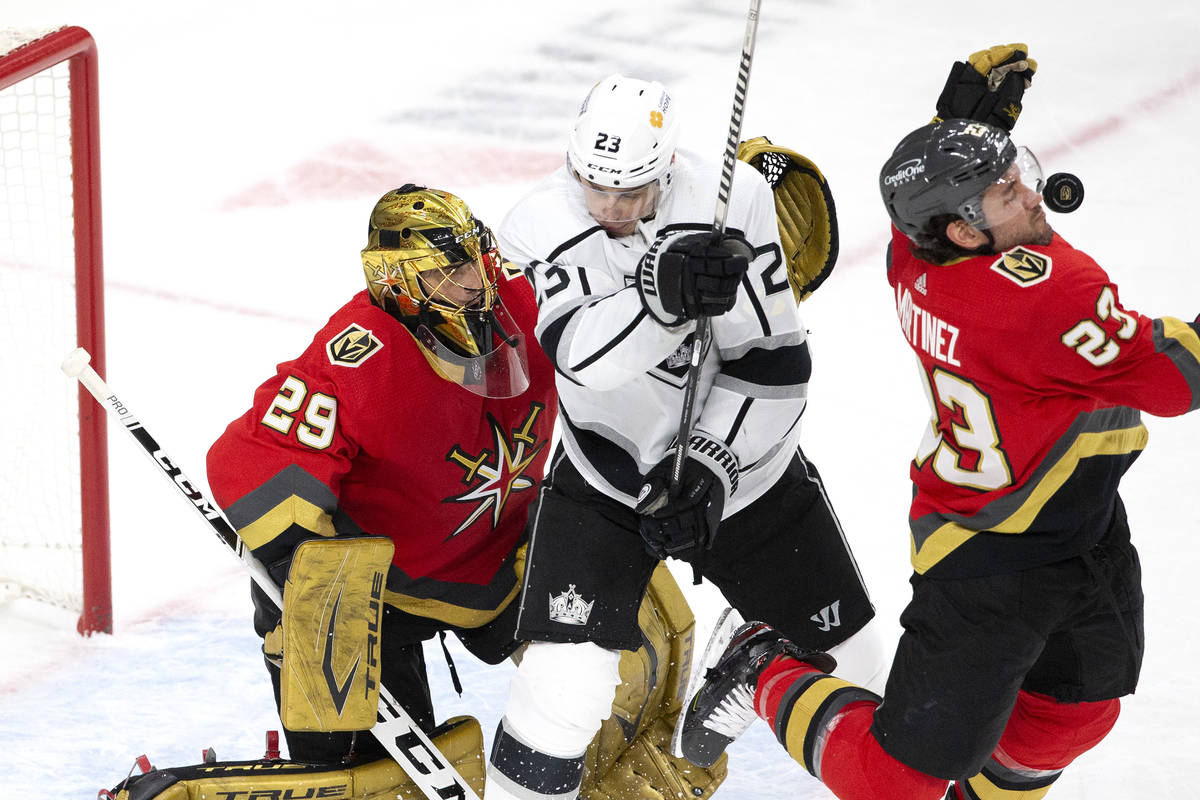 Golden Knights defenseman Alec Martinez (23) takes a puck to the face while defending as Kings ...