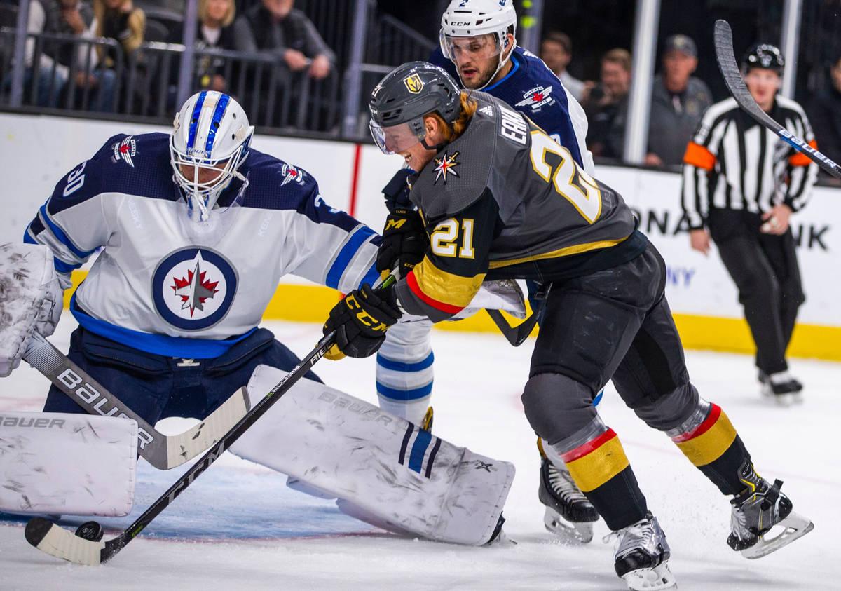 Winnipeg Jets goaltender Laurent Brossoit (30) gets a pad on a shot by Vegas Golden Knights cen ...