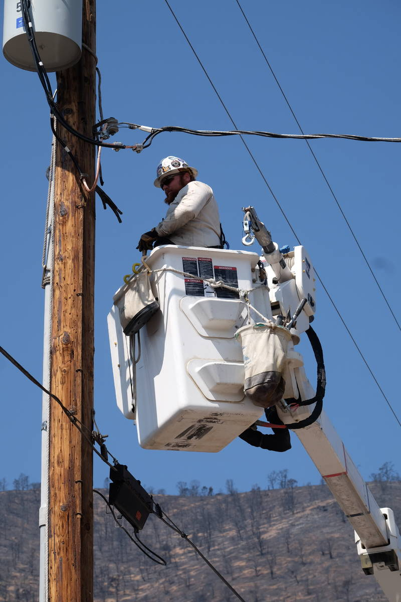 A utility worker repairs power lines at a burned-our subdivision partially destroyed by the Tam ...