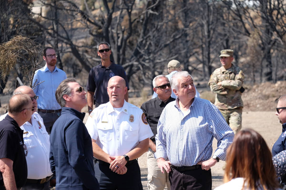 Govs. Gavin Newsom of California and Steve Sisolak of Nevada look over the remains of a home th ...