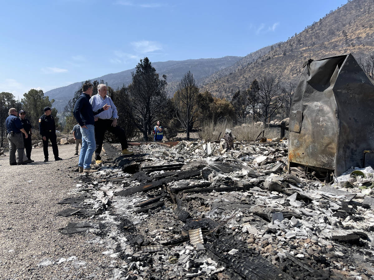 Govs. Newsom and Sisolak confer and look over the remains of a home in Gardnerville, NV, destro ...