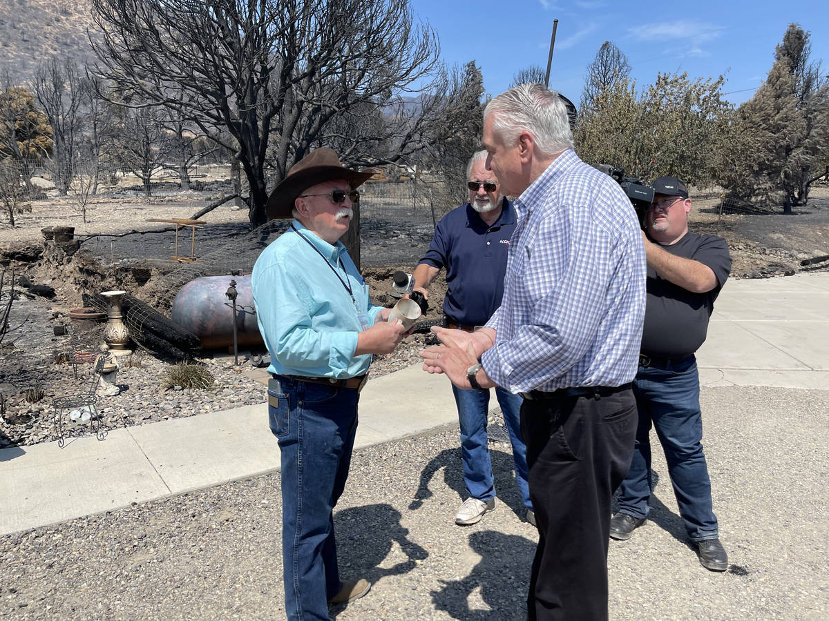 Gov. Steve Sisolak speaking to an area resident who helped others evacuate ahead of the the Tam ...