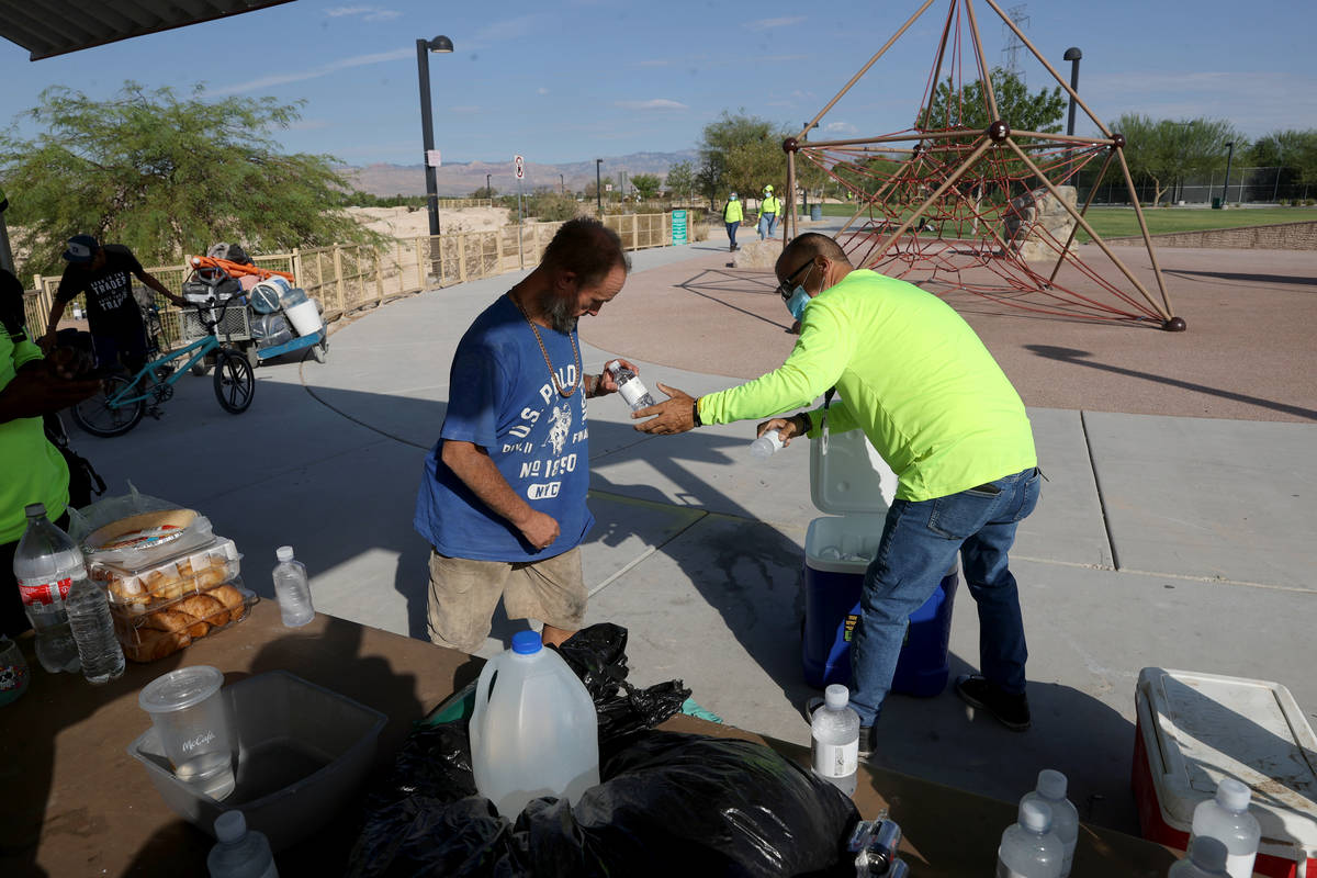 HELP of Southern Nevada Director of Crisis Teams Louis Lacey, right, gives water to Carl Nickel ...