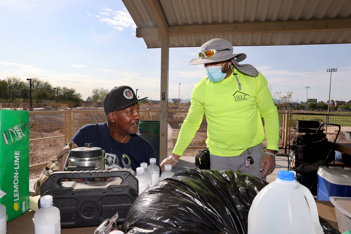 HELP of Southern Nevada outreach worker Abdul Hamdard gives water to Earl Howard, 62, during an ...
