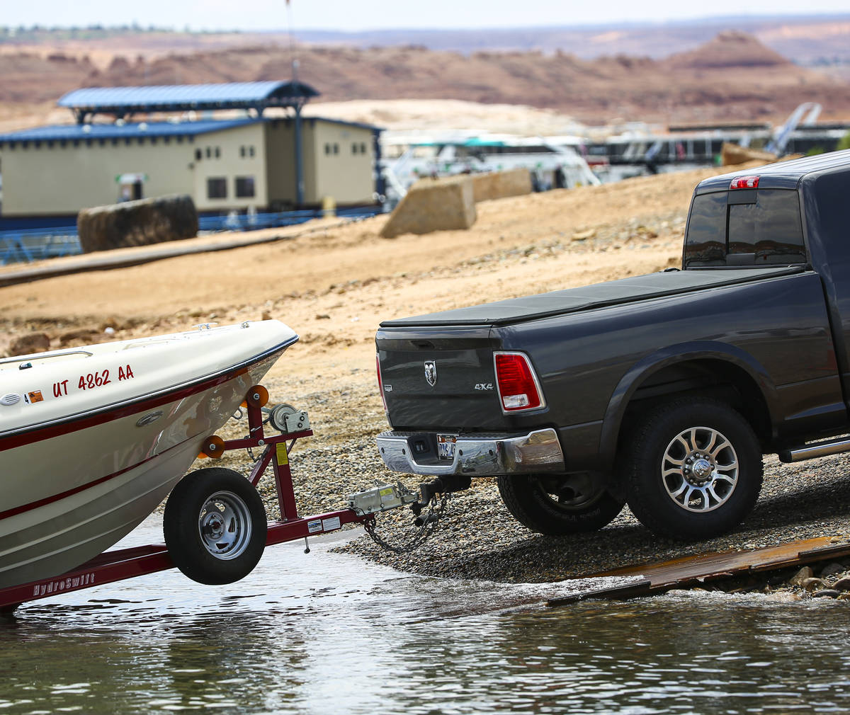 A truck rests on pipe matting while waiting to remove a boat at the Wahweap main launch ramp at ...