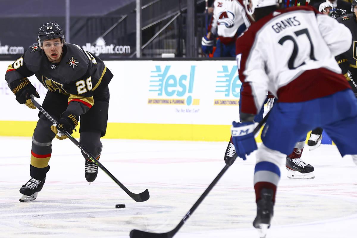 Golden Knights' Mattias Janmark (26) looks to skate past Colorado Avalanche's Ryan Graves (27) ...