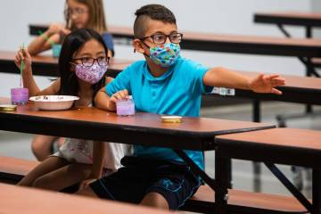 Ellura H., 8, and Giani B., 8, mix paints in the cafeteria as Giani reaches towards another cam ...