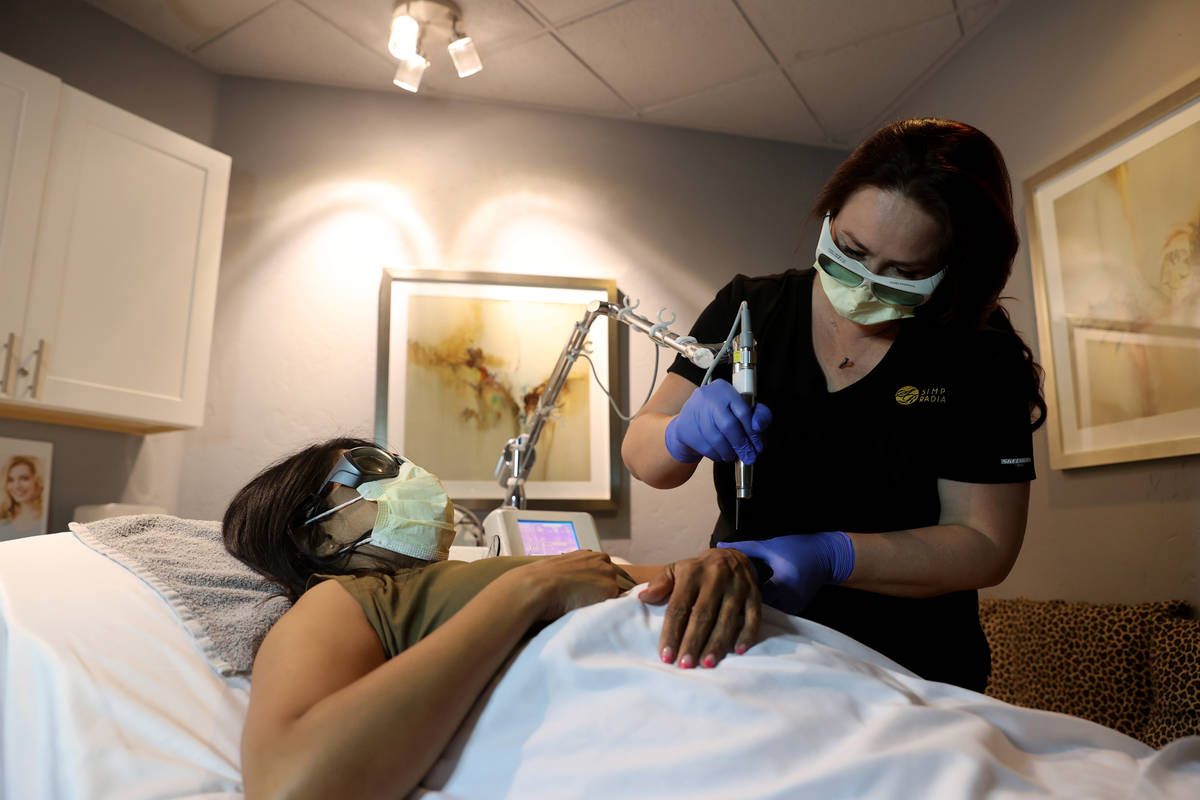 Laser technician Jennifer Knepper does hair removal on client Netrani Sharma at Simply Radiant ...