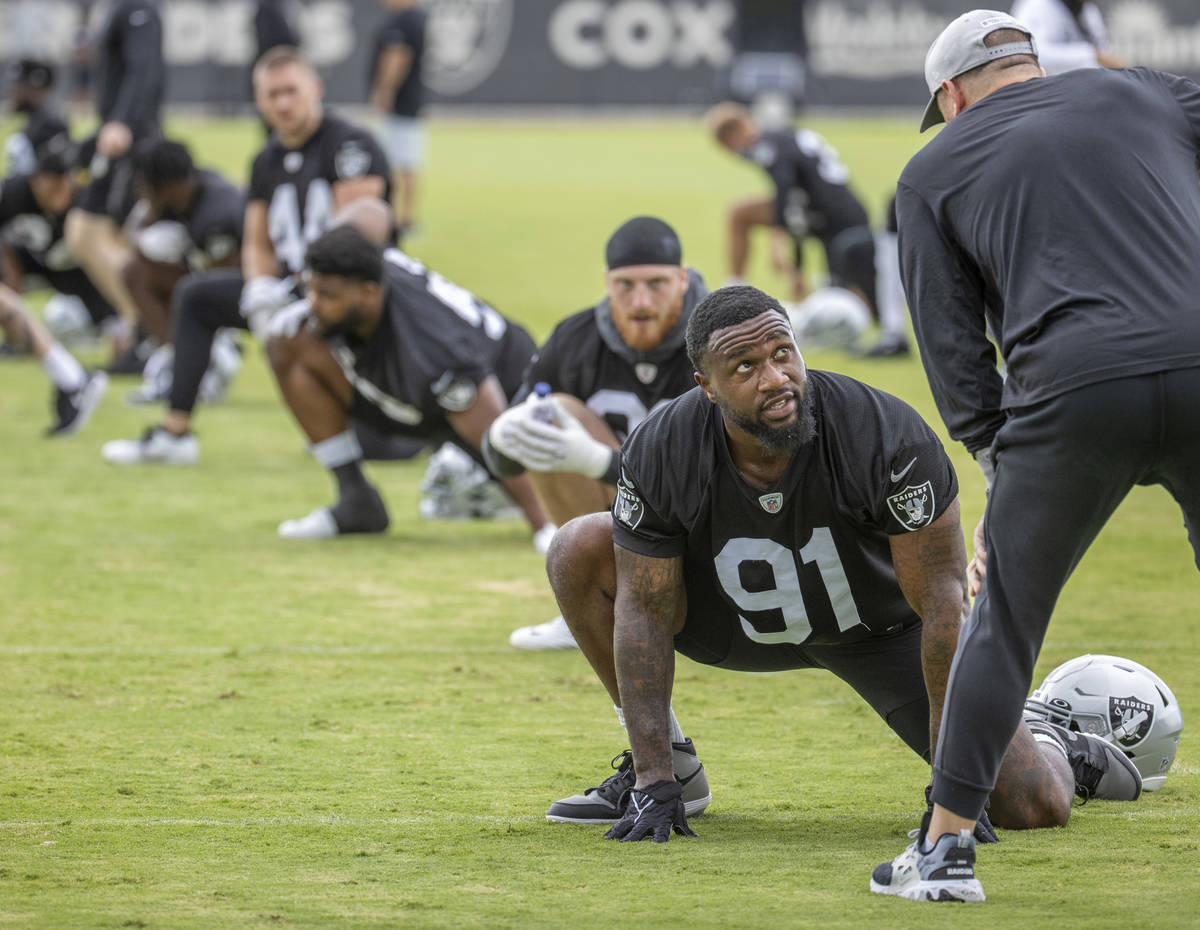 Raiders defensive end Yannick Ngakoue (91) confers with staff during training camp at the Inter ...